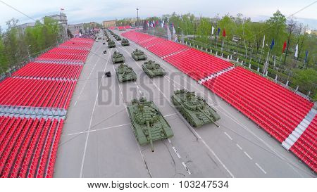SAMARA - MAY 06, 2015: Military motorcade with tanks moves along empty tribunes during parade rehearsal at spring evening. Aerial view video frame