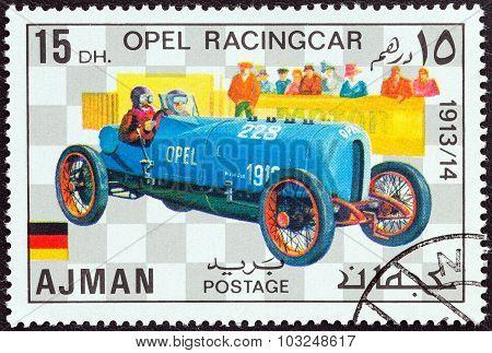AJMAN EMIRATE - CIRCA 1971: Stamp shows Opel racingcar of 1913
