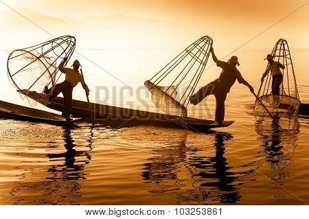 Burmese fisherman on bamboo boat catching fish. Inle lake Myanmar