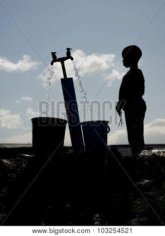 Silhouette of child getting water