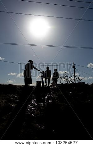 Silhouette of family getting water