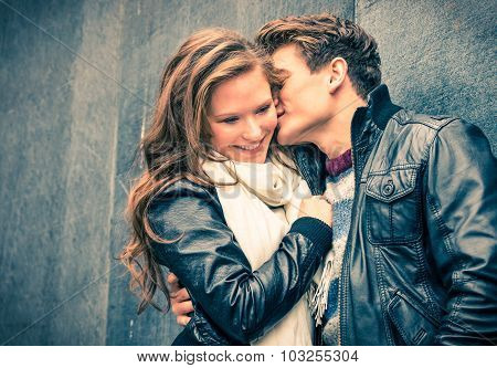 Young happy couple in love at beginning of love story - Handsome man whispers soft kisses in young woman ear - Fall fashion concept with boyfriend and girlfriend on a cold vintage filtered look poster