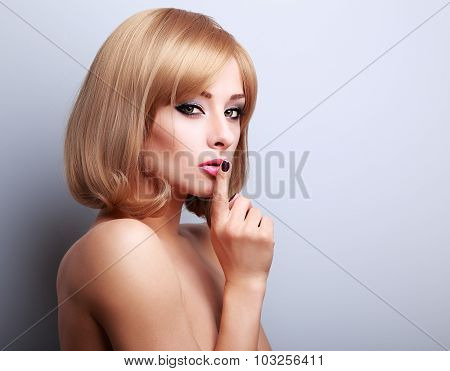 Sexy Beautiful Makeup Blonde Famale Model Showing Secret Sign On Blue