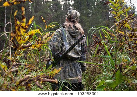 Woman hunter in camouflage with gun on the riverside poster