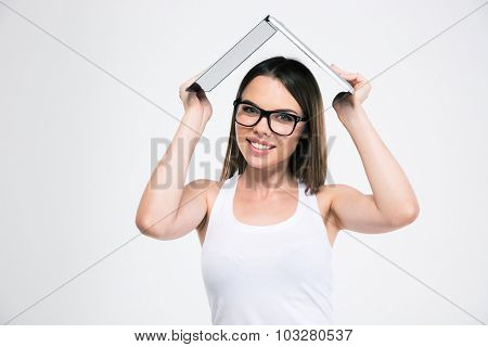 Portrait of a smiling female student holding laptop computer over head isolated on aw hite background