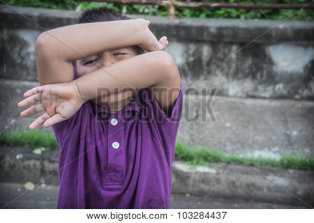 Scared young boy covering face with hands