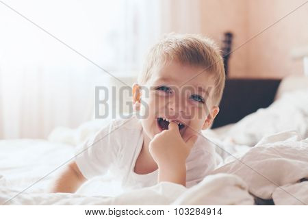 2 years old little boy dressed in pajamas are relaxing and playing in the parent's bed, warm and cozy scene. Pastel colors, selective focus.