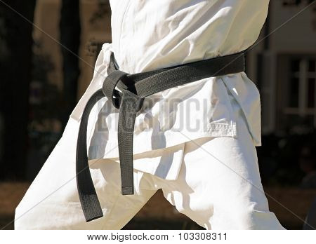 black belt with a combat sport, close up on a fighter