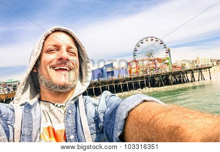 Handsome man taking a selfie at Santa Monica Pier with ferris wheel - Sunny day in California coast - Adventure travel lifestyle around United States of America - Composition with tilted horizon poster