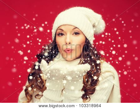 christmas, x-mas, people, happiness concept - happy woman in winter clothes blowing on palms