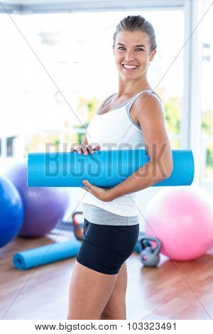 Side view of woman smiling while holding yoga mat in fitness studio
