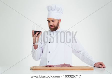 Portrait of a handsome male chef cook degusting wine isolated on a white background