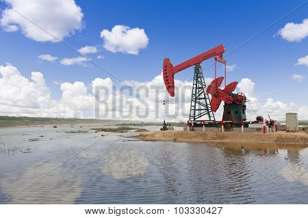 A red oil pump by the riverside