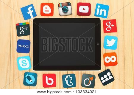 Famous social media icons  placed around iPad on wooden background