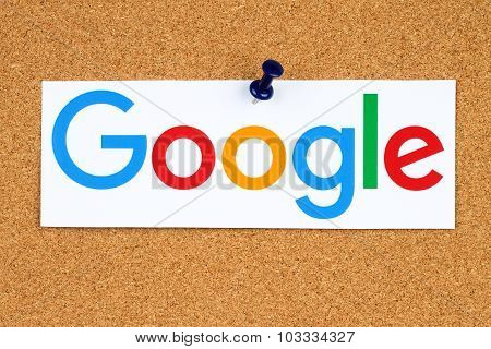 New Google logotype printed on paper cut and pinned on cork bulletin