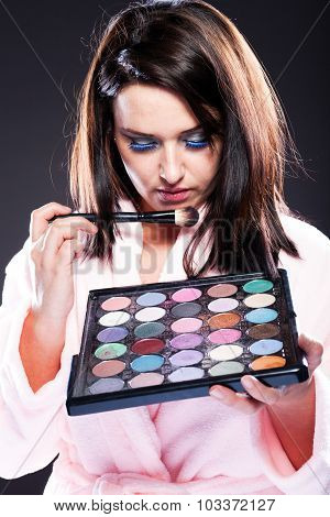 Woman in bathrobe and make up palette poster