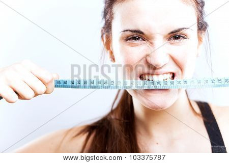 Angry Young Woman Biting Measuring Tape