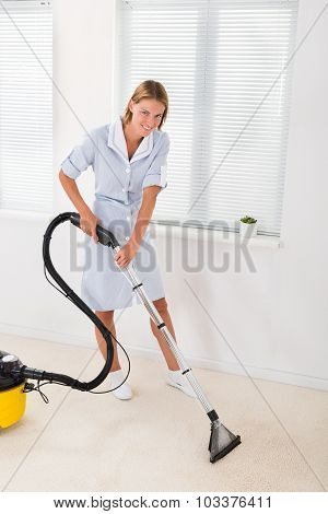 Young Female Maid In Uniform Vacuuming Floor poster