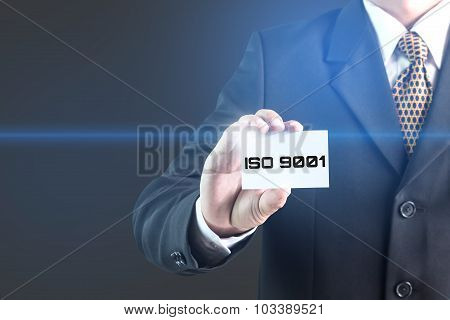 Businessman in a data center selecting a label with iso 9001 poster