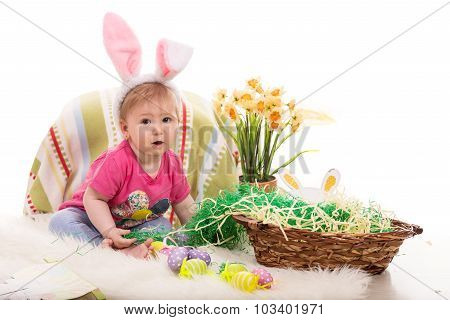 Beautiful baby girl sitting in Easter decor and wearing fluffy bunny ears