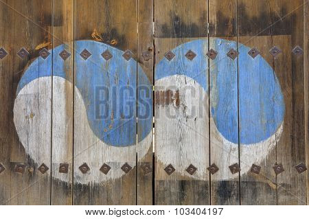 The Ying Yang sign painted on old wooden door
