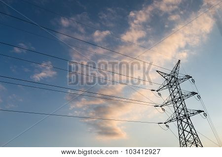 A Long Line Of Electrical Transmission Towers (electricity Pylons) Carrying High Voltage Lines In Th