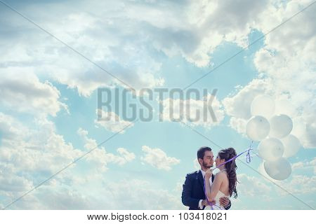 Just Married Bride And Groom With Baloons In Hand Over Cloudy Sky