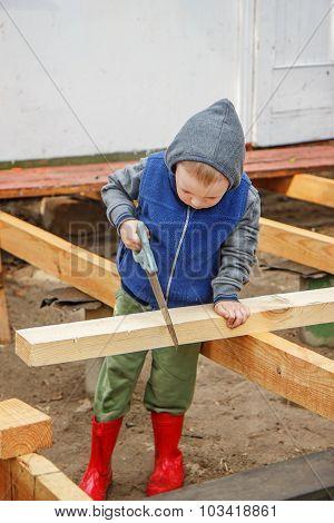 Little Studious Boy Sawing A Wooden Board. Home Construction. Little Builder.