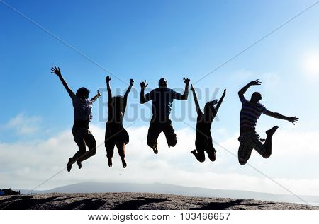 Silhouettes of group of friends jumping outdoors on a beach in unison with arms up
