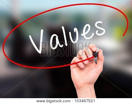 Man Hand writing Values with black marker on visual screen.