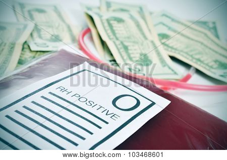 closeup of a blood bag with a label with the text O RH positive and a pile of US dollar bills in the background