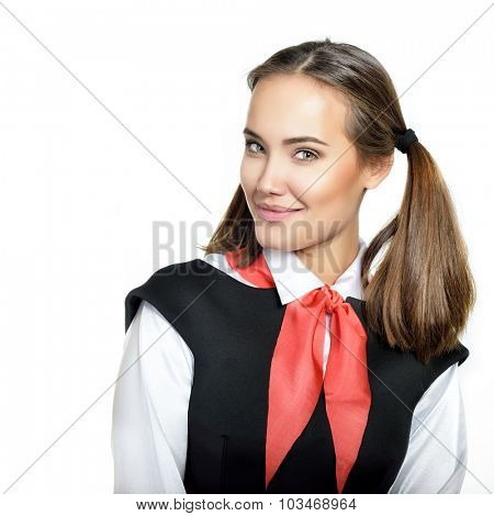 Young Pioneer dressed in school soviet with red scarf smiling and looking at camera. Beautiful girl posing like a Pioneer from USSR. Product of the twentieth century.