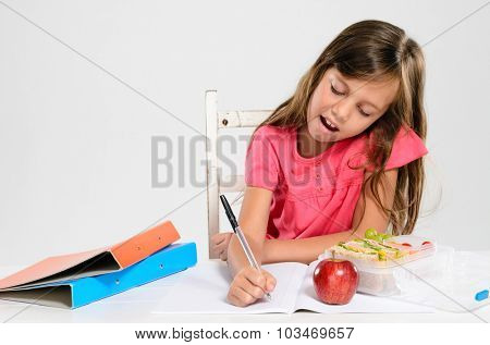 Hardworking studious cute school girl writes and does her homework with an apple and healthy packed lunch on the table