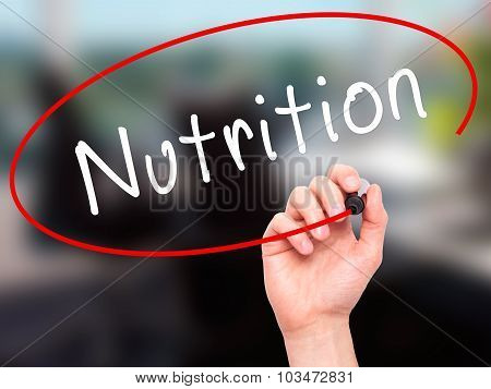 Man Hand writing Nutrition with marker on transparent wipe board.
