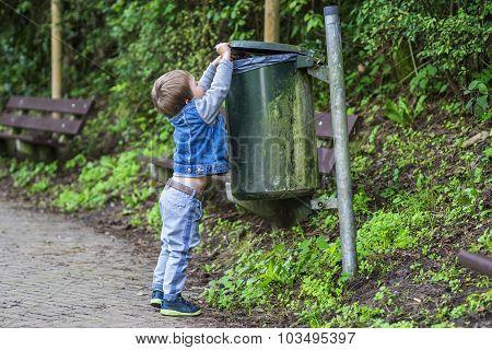Little Boy Throwing Trash In The Bin