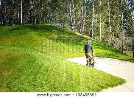 Man Mowing Lawn On Golf Course Using Lawn-mower