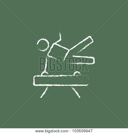 Gymnast on pommel horse hand drawn in chalk on a blackboard vector white icon isolated on a green background.