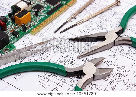 Printed circuit board with electrical components and precision tools lying on construction drawing of electronics drawings and tools for engineer jobs technology poster