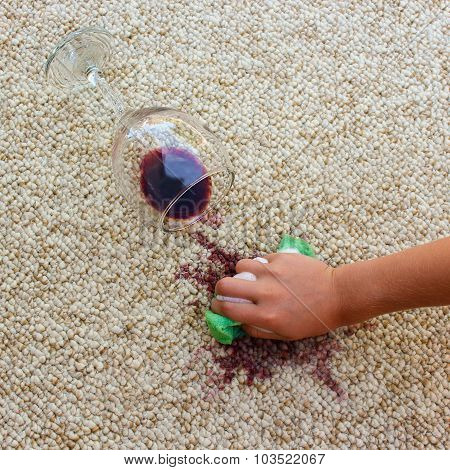 glass of red wine fell on carpet, wine spilled on carpet. Female hand cleans the carpet with a spong