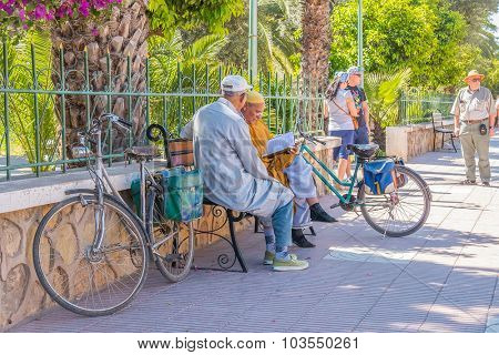 TAROUDANT, MOROCCO, APRIL 9, 2015: Local men study Quran on bench