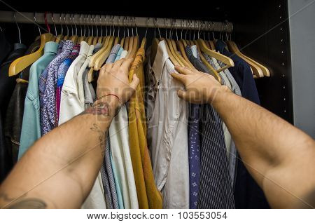 Man searching for a shirt in his wardrobe