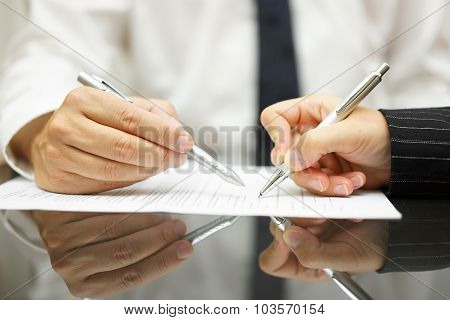 Business Man Is Showing With Pen To Business Woman Where To Sign Document