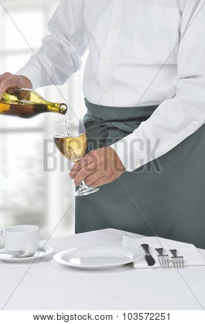 Waiter Pouring a Glass of Chardonnay Wine in a modern restaurant. Man is unrecognizable.
