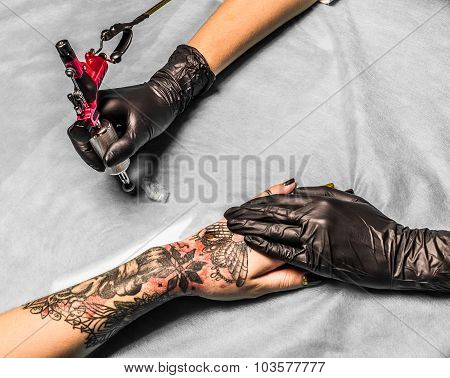 Tattoo master take paint in salon for tattoo on girls hand. Tattooist works in professional salon with pink tattoo machine on a blue mat and in sterile black gloves. poster