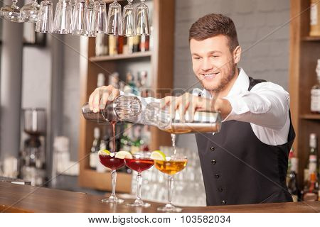 Attractive young barman is making drinks in pub