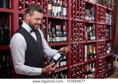 Attractive male sommelier is working in shop