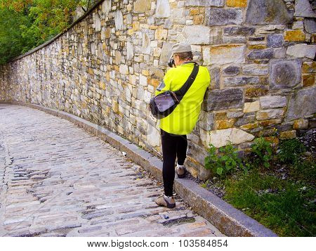 Senior Tourist Photographs Walls Of Historic Old Quebec