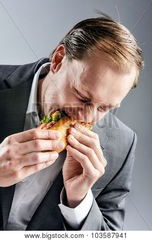 Hungry man in business suit devours BLT baguette with big greedy bite