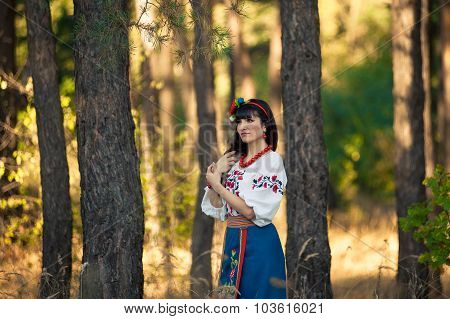 Young woman in national ukrainian clothes on the wheat field