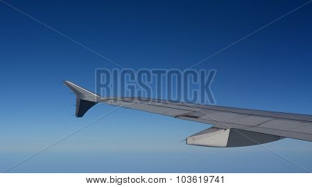 Wing Of Airplane Flying Above The Clouds